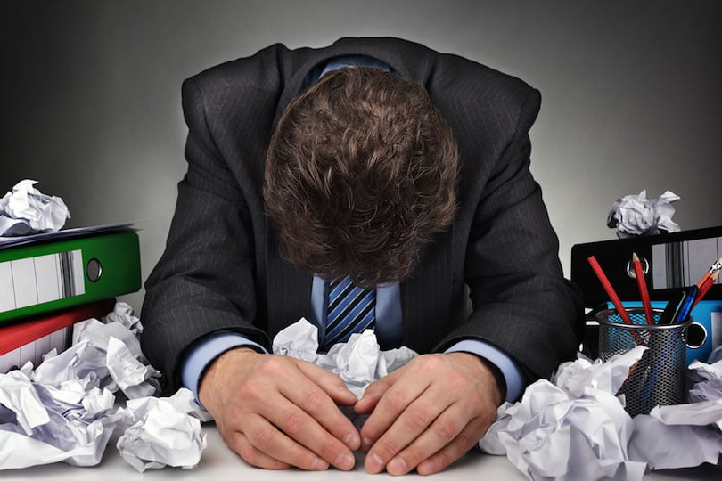 Overworked, depressed and exhausted businessman at his desk with a pile of work or concept for frust